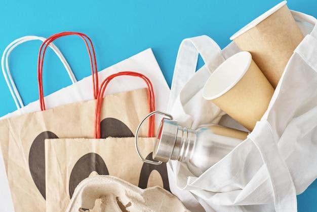 Zero conceito de desperdício. itens reutilizáveis ecológicos em sacola de compras natural. saco de papel, xícaras de café e garrafa de metal em um azul