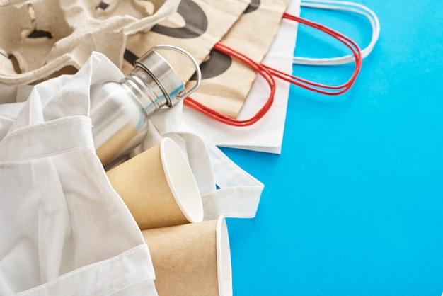 Zero conceito de desperdício. itens reutilizáveis ecológicos em sacola de compras natural. saco de papel, xícaras de café e garrafa de metal