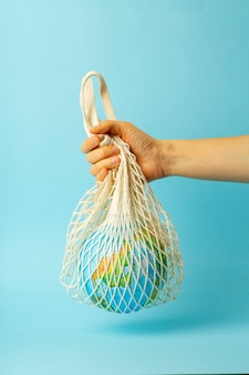 Zero conceito de desperdício. saco de cordas em uma mão feminina com o globo da terra. sacos de plástico grátis