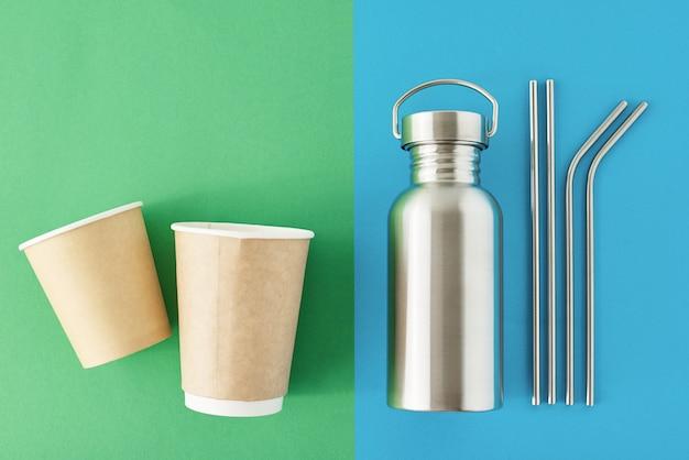 Zero conceito eco desperdício. itens livres de plástico reutilizáveis em uma superfície azul e verde colorida. vista superior da garrafa de alumínio, tubos de metal e copos de café de papel