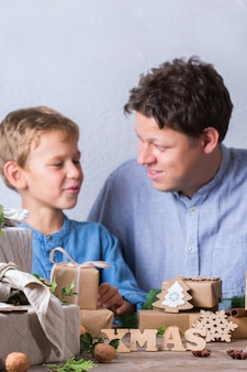 Zero desperdício de conceito de natal pai e filho embrulhando presentes Foto Premium