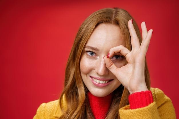 Zero preocupa apenas a felicidade. retrato de mulher ruiva encantadora fofa e despreocupada com sardas e olhos azuis, sorrindo encantado, mostrando o gesto bem no olho e espreitando para a câmera sobre fundo vermelho.