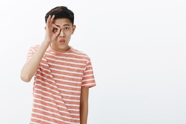 Zero preocupação. retrato de jovem bonito e elegante menino asiático em camiseta listrada fazendo um gesto de aprovação no olho
