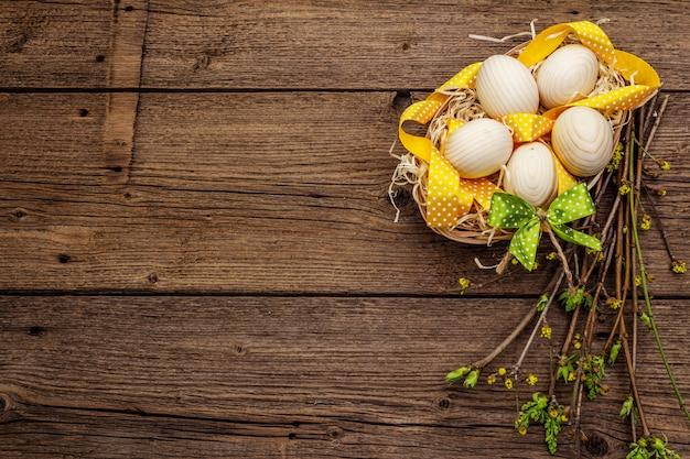 Zero resíduos conceito de páscoa. galhos de primavera com folhas verdes frescas, ovos de madeira na cesta, fita de bolinhas