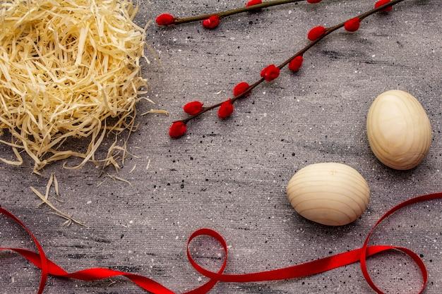 Zero resíduos conceito de páscoa. ovo de madeira, ninho de pássaro, fita de cetim, selos de salgueiro vermelho. sem plástico, tendência ecológica. fundo de concreto cinza