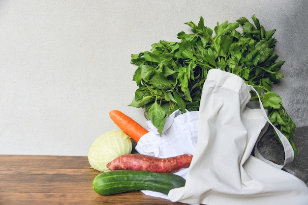 Zero resíduos usam menos conceito de plástico / legumes frescos orgânicos em sacos de tecido de algodão eco na mesa de madeira