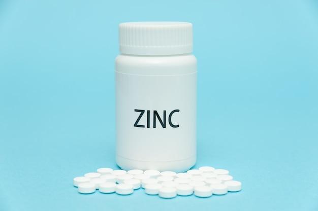 Zinco em embalagem de frasco branco com comprimidos espalhados. suplemento nutricional.