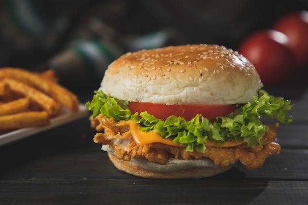 Zinger burger na mesa de madeira escura com batatas fritas e tomate no fundo