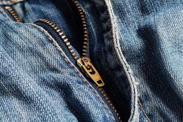 Zíper de bronze manchado de metal com fundo azul jeans deslizante close-up foco seletivo costura artesanal costura