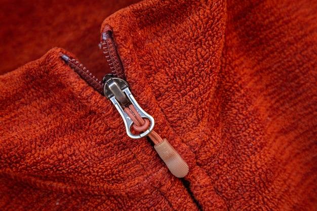 Zíper zíper close-up macro sobre fundo de roupas vermelhas