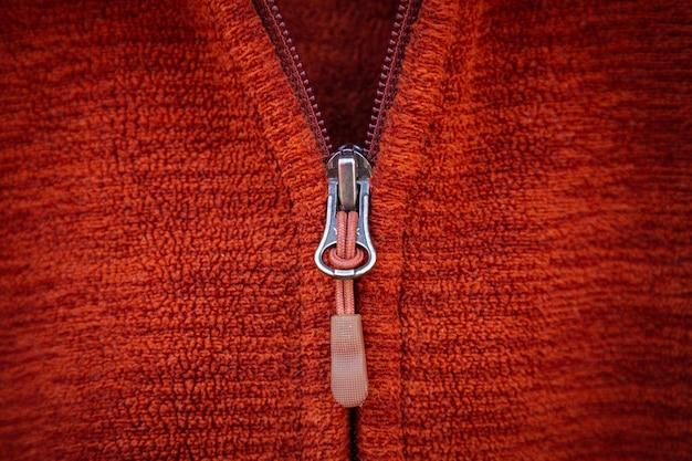 Zíper zíper fechar macro sobre fundo de roupas vermelhas.