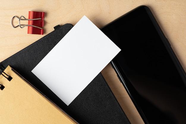 Zombar de cartão de visita em branco e tela preta smartphone na mesa
