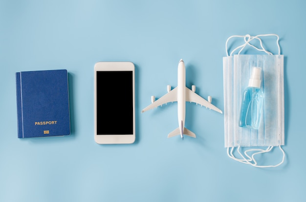 Zombar de smartphone com modelo de avião, passaportes, máscara facial e spray desinfetante para as mãos
