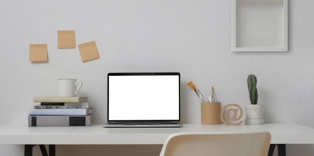 Zombar do computador portátil em local de trabalho mínimo com ferramentas de pintura e material de escritório