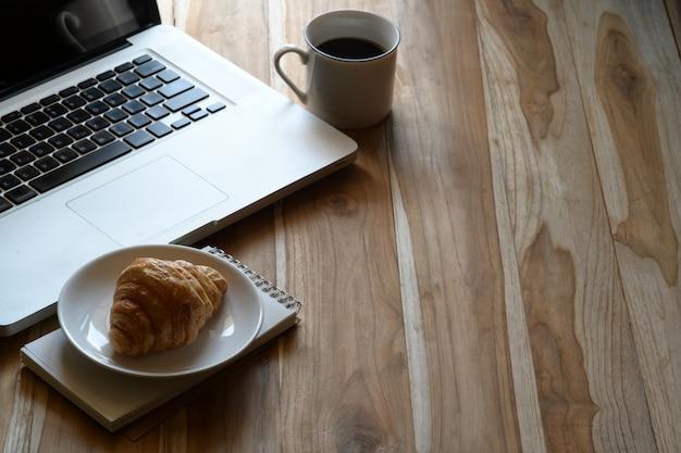 Zombe acima do portátil do espaço da mesa, do café e do croissant na tabela de trabalho de madeira.