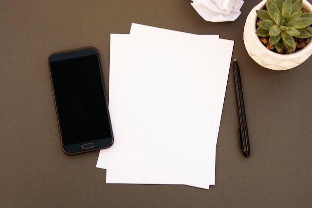 Zombe acima do smartphone, pappers vazios, planta suculento, acessórios do escritório no fundo cinzento com espaço da cópia, configuração lisa. mesa de trabalho de estilo minimalista.