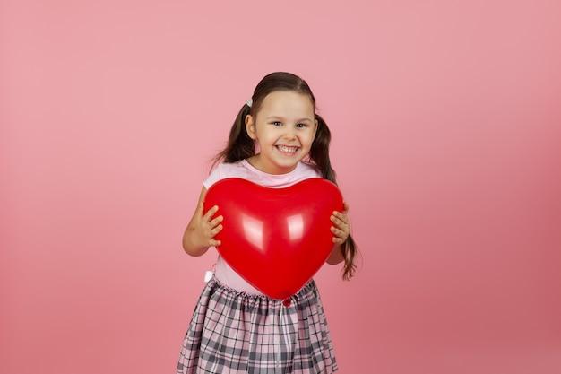 Zombe de admiração da garota maravilhada com um vestido rosa segurando um balão vermelho em forma de coração