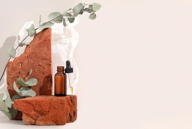 Zombe de frasco de vidro marrom com soro conta-gotas na pedra vermelha e fundo bege com papel amassado. brutal. copie o espaço. peeling de ácido, óleo facial, colágeno