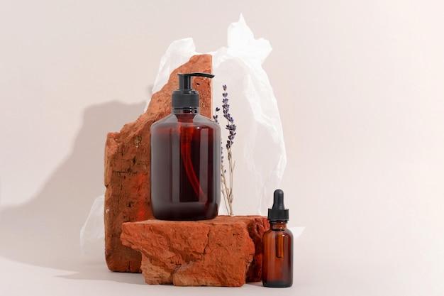 Zombe de frasco de vidro marrom com soro conta-gotas na pedra vermelha e fundo bege com papel amassado. frasco de plástico com dispensador de sabonete, gel de banho. copiar espaço peeling ácido, óleo facial, colágeno.