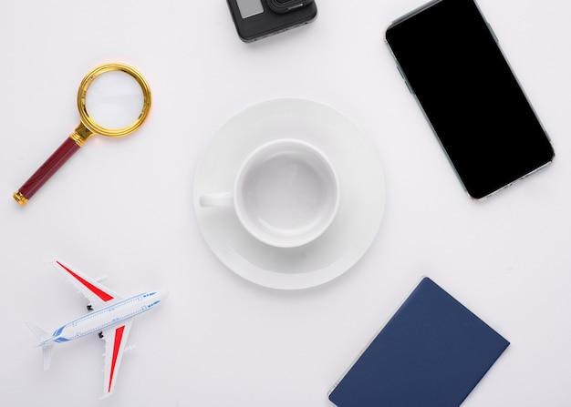 Zombe de lupa de férias, passaporte, telefone, câmera de ação, avião e um copo vazio no fundo branco