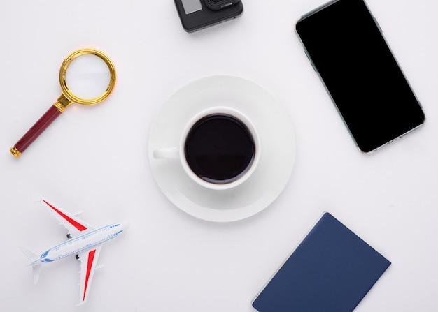 Zombe de lupa de férias, passaporte, telefone, câmera de ação, avião e uma xícara de café no fundo branco