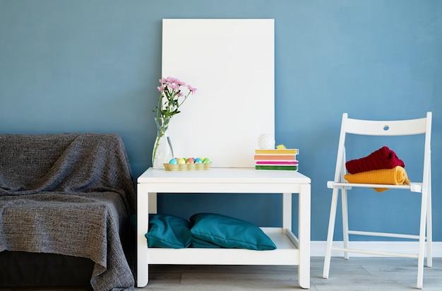 Zombe de moldura branca na mesa de centro na sala azul. tela em branco em branco no interior