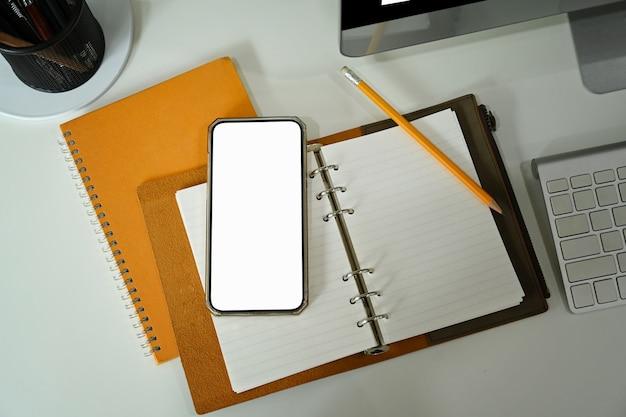Zombe de telefone inteligente, caderno e xícara de café na mesa branca.