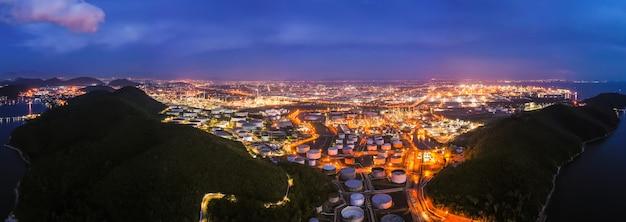 Zona da indústria petrolífera da refinaria na noite sobre o colorido e a iluminação com a antena do céu azul