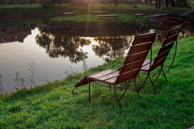 Zona de descanso. cadeiras de madeira estão na grama à beira do lago, de frente para o lago.
