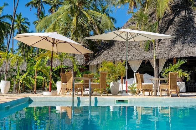 Zona de descanso perto da piscina em uma praia tropical na ilha de zanzibar, tanzânia, áfrica. conceito de verão, viagens, férias e férias