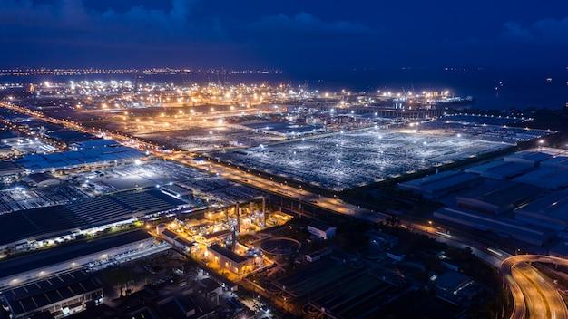 Zona de fábrica de vista aérea e porto de embarque no mar à noite