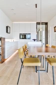 Zona de jantar com mesa, cadeiras e lâmpadas suspensas em apartamento moderno e minimalista com cozinha de conceito aberto