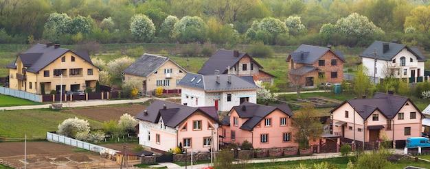 Zona suburbana residencial tranquila. rua com novas casas de tijolo confortável moderno com jardas e jardins florescendo no fundo da bela floresta verde. investimentos no conceito imobiliário.