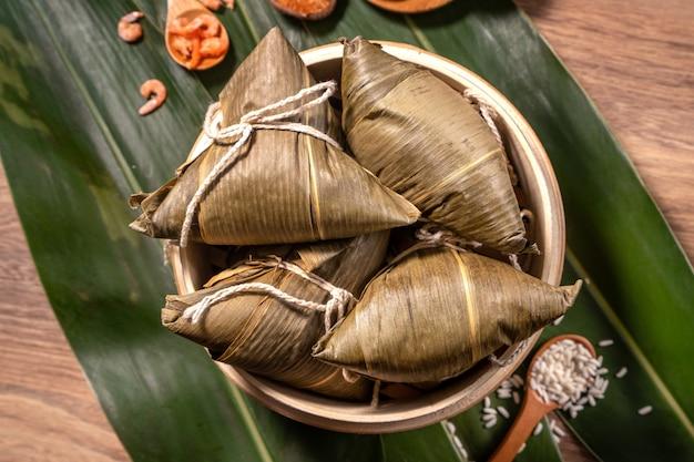 Zongzi, bolinhos de arroz cozido no vapor em folhas de bambu de mesa de madeira, comida no conceito duanwu do festival de barco dragão, close-up, cópia espaço, vista superior, lay plana