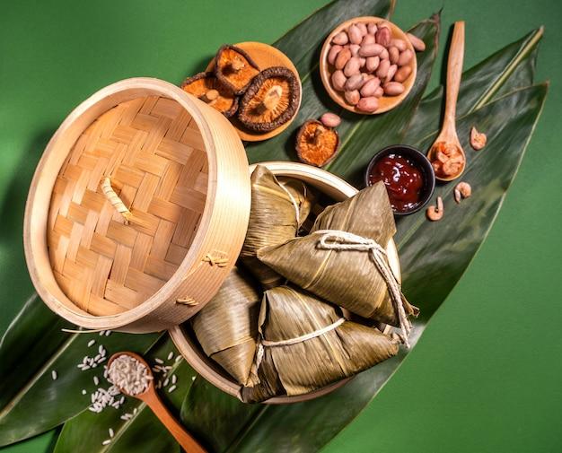 Zongzi, bolinhos de arroz cozido no vapor no fundo da mesa verde, comida no conceito duanwu do festival de barco do dragão, close-up, cópia espaço, vista superior, lay plana