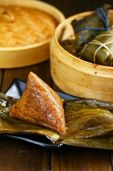 Zongzi de bolinhos de arroz e vapor de bambu na mesa de madeira