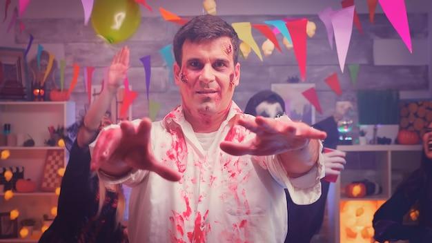Zoom do retrato na cena de um zumbi assustador em uma festa de halloween com os amigos de seus personagens se divertindo ao fundo