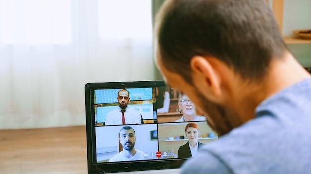 Zoom out do homem em uma videochamada com sua equipe de trabalho durante o bloqueio covid-19.