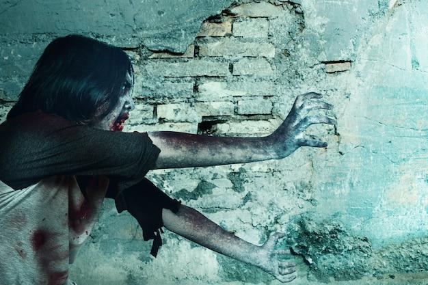 Zumbi assustador com sangue e ferida em seu corpo caminhando com uma parede rachada