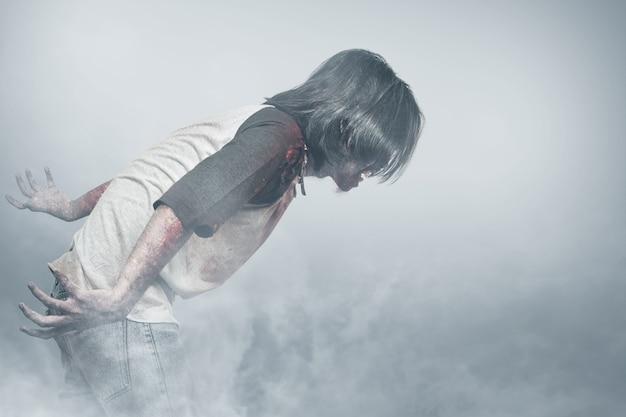 Zumbi assustador com sangue e ferida em seu corpo parado na névoa