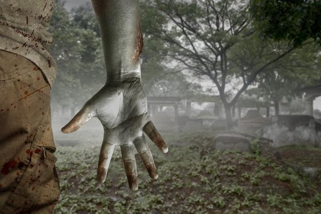 Zumbi assustador com sangue e ferida no corpo caminhando no cemitério