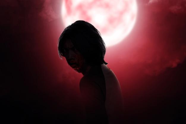 Zumbi assustador com sangue e ferida no corpo em pé com uma cena noturna de fundo