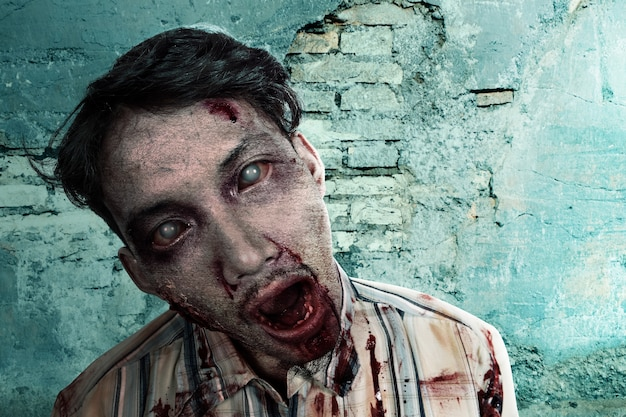 Zumbi assustador com sangue e ferida no corpo em pé com uma parede rachada