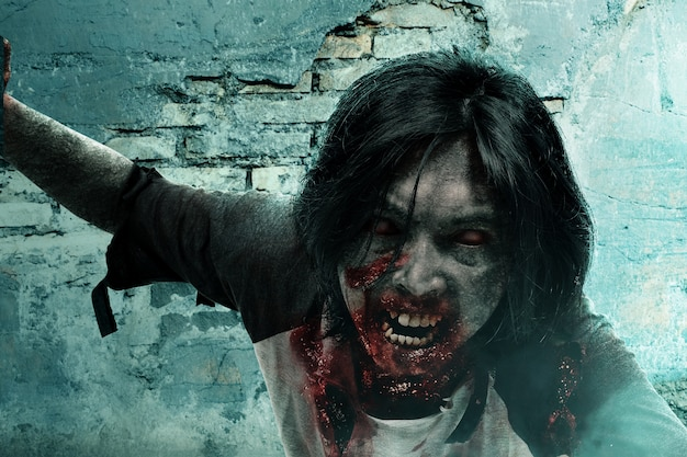 Zumbi assustador com sangue e ferida no corpo rastejando por uma parede rachada