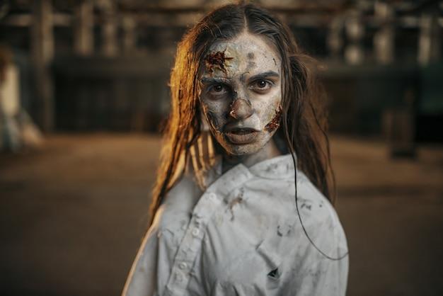 Zumbi feminina caminhando em uma fábrica abandonada, horror
