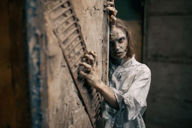 Zumbi feminino em uma fábrica abandonada, diabo. terror na cidade, ataque de rastejadores assustadores, apocalipse do fim do mundo, monstros malignos sangrentos