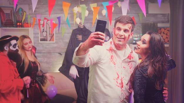 Zumbi perigoso e bruxa assustadora tirando uma selfie na festa de halloween em casa decorada