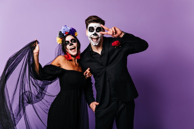 Zumbis mexicanos maravilhosos expressando felicidade. menina charmosa muerte comemorando o dia das bruxas com o namorado.