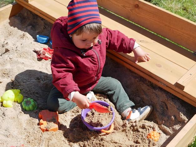 1-2 jähriger junge spielt im sandkasten