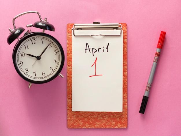 1. april narrentag, notizbuch, uhr, stift. flache lage auf rosa hintergrund.